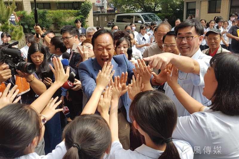郭台銘走進新竹市私立曙光女中,受到女同學們列隊擊掌的熱情歡迎。(圖/方詠騰攝)