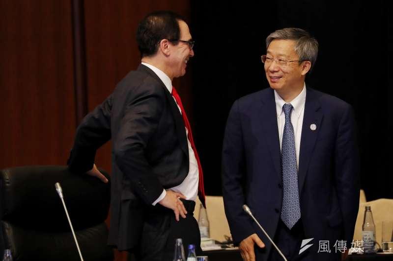 中國人民銀行行長易綱(右)在新一期 「中國金融」上發表題為「盡可能長時間實施正常貨幣政策,促進居民儲蓄和收入合理增長」的文章。(AP)