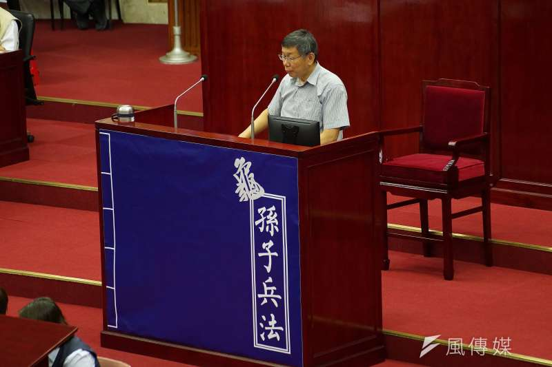 台北市長柯文哲出席市政總質詢,議員王世堅在質詢台上,貼「龜孫子兵法」海報暗諷他。(盧逸峰攝)