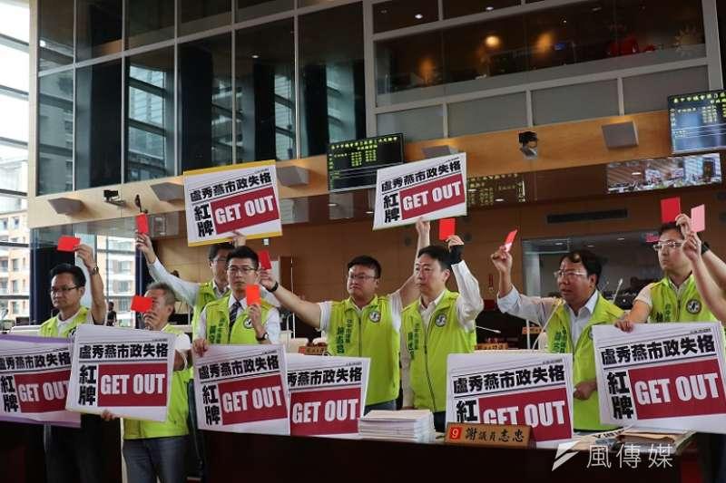 九位民進黨議員吼地聲嘶力竭,舉著紅牌將市府團隊請出議場。(王秀禾攝)