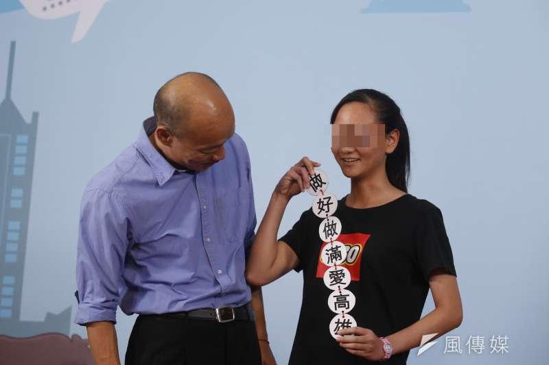 高雄市長韓國瑜(左)25日出席高中模範生畢典頒獎,一名女同學手持「做好做滿愛高雄」標語諷刺韓國瑜。(資料照,新新聞郭晉瑋攝)
