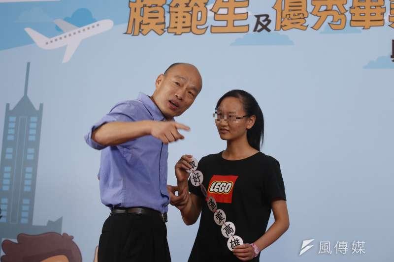 高雄市長韓國瑜(右)25日出席新莊高級中學模範生、市長獎畢業典禮,一名女同學(左)上台時,手持「做好做滿愛高雄」標語。(資料照,新新聞郭晉瑋攝)