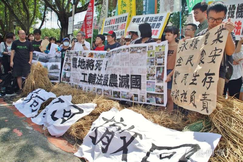 多個環團27日上午赴立法院前丟稻草,抗議惡法通過將「毀農滅國」,要求立法院暫停修法。(盧逸峰攝)