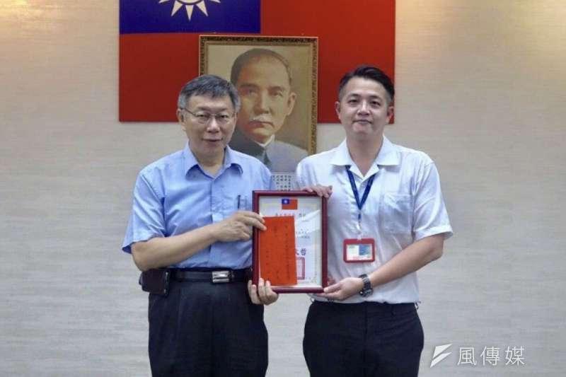 台北市長柯文哲(左)於7月治安會報,頒發感謝狀及禮券表揚攔阻詐騙有功人員。(台北市警察局提供)