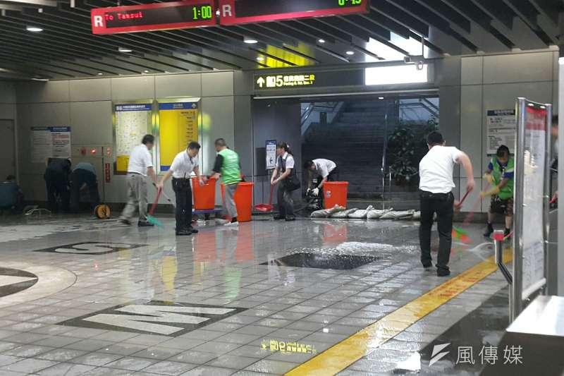 20190722-台北市22日午後暴雨導致大安區及長安東路等多處積水,圖為捷運大安站人員清理站內進水、堆放沙包阻水。(朱冠諭攝)
