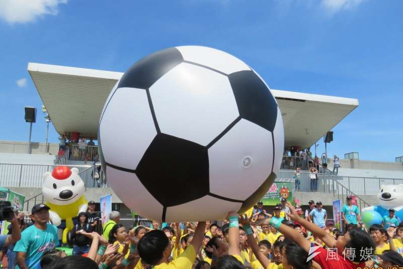 現場來賓與小球員們合力推動超大型足球,象徵台電2019足球FUN電營正式開訓。(圖/方詠騰攝)