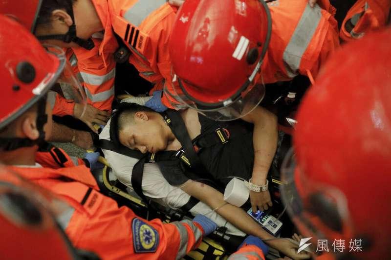 一名據稱是中國公安的黑衣人一度被抗議群眾控制,救護人員試圖將他帶離現場。(美聯社)