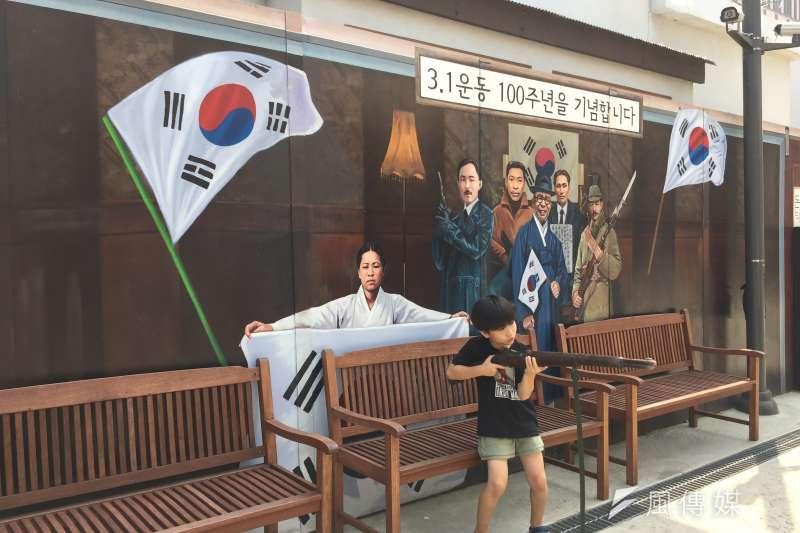 首爾敦義門博物館村:孩童在紀念南韓抗日「三一運動」的壁畫前留念。(鍾巧庭攝)