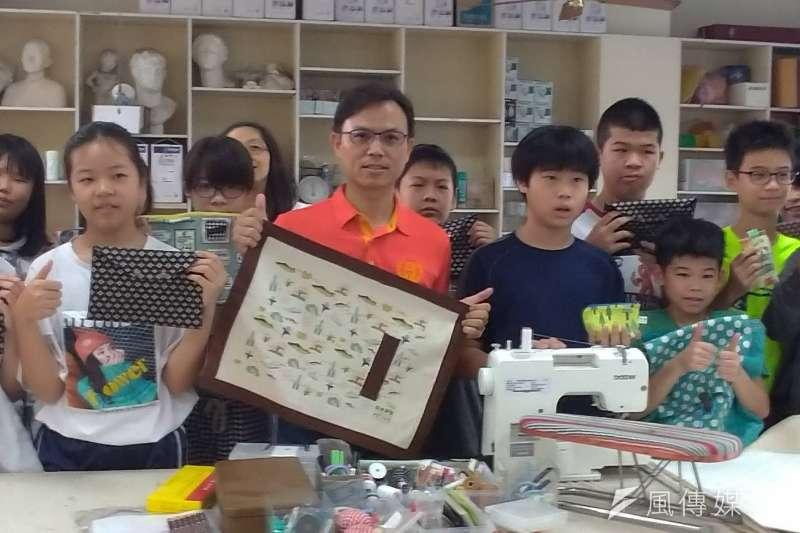 忠孝國小校長楊頌平(中)與拿著親手縫製布藝用品的學生們開心合照。(圖/徐炳文攝)