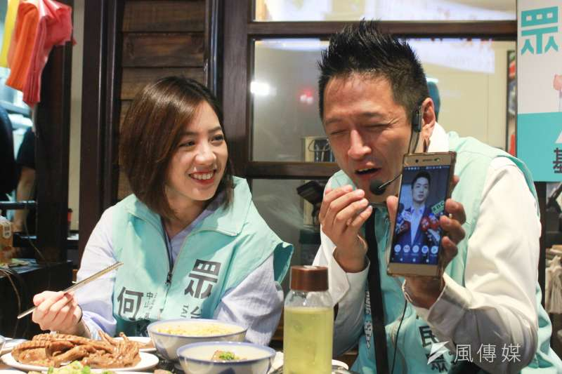 台北市副發言人黃瀞瑩(左)今晚陪民眾黨台北市立委參選人何景榮(右)掃街拜票,何景榮在直播過程中,秀出手機中對手蔣萬安的照片。(方炳超攝)