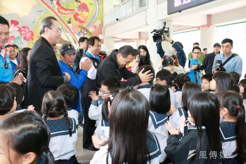 新北市長侯友宜前往板橋區新埔國小視察受到小朋友熱情歡迎,他也開心與他們互動。  (圖/李梅瑛攝)