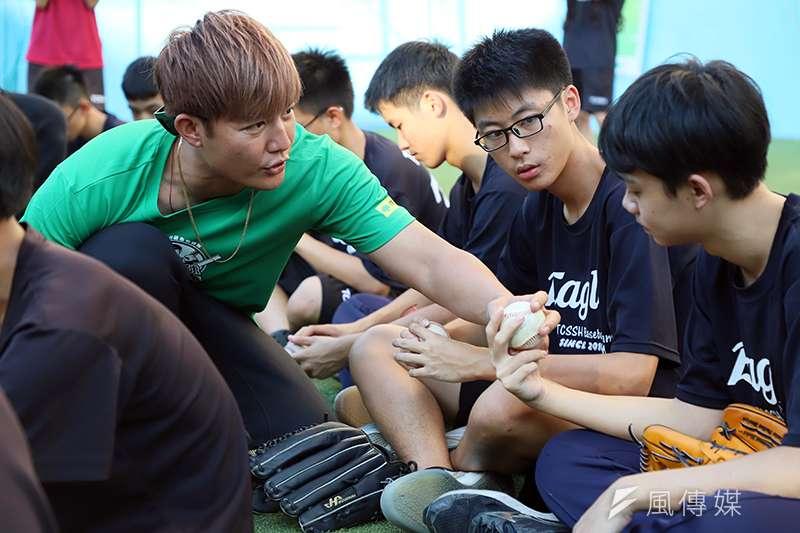 王維中(左)仔細指導台中二中棒球社的同學變化球的握法。(余柏翰攝)