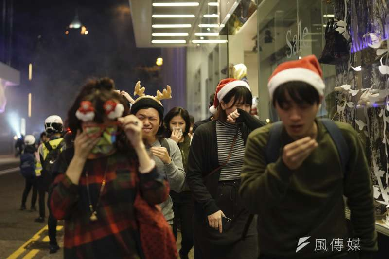 香港警察在耶誕夜施放催淚彈,行人紛紛掩住口鼻。(AP)