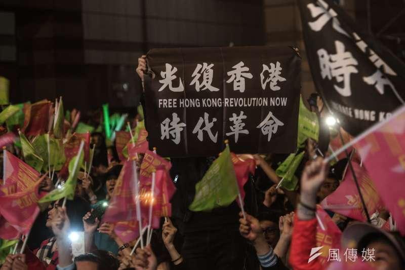 總統蔡英文票數持續大幅領先國民黨總統候選人韓國瑜,連任在望,不少支持者在民進黨競選總部前手舉支持香港「反送中」的標語。(簡必丞攝)