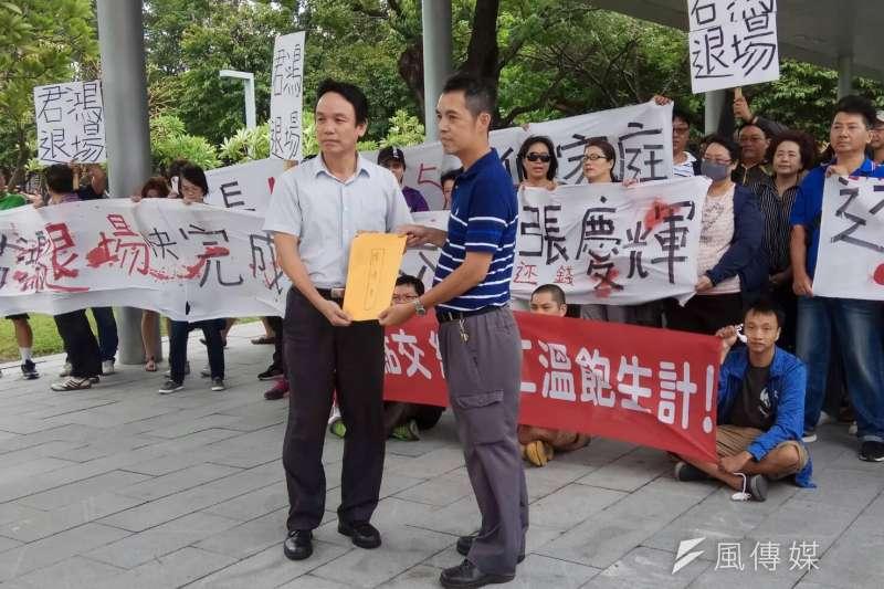 高雄市勞工局主任秘書皮忠謀(左)接受勞工代表陳情書。(圖/徐炳文攝)