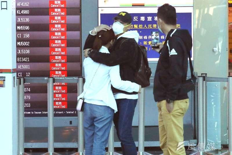 20200326-因武漢肺炎疫情管控出入境,桃園機場單日出入境人數已跌破萬人,圖為一對準備出境的旅客在出境大廳離情依依互相擁抱.(柯承惠攝).