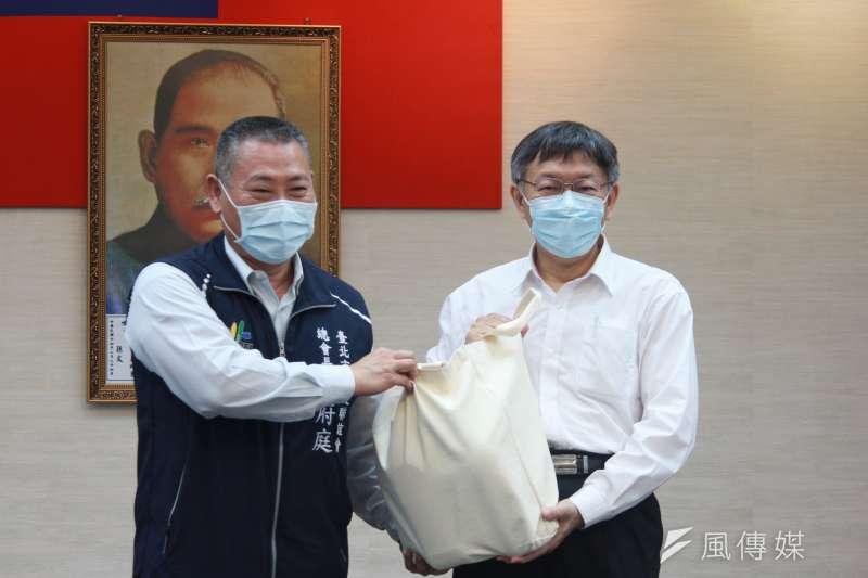 台北市政府26日下午再召開疫情小組應變會議,台北市長柯文哲(右)配分防疫包給各區里長。(方炳超攝)