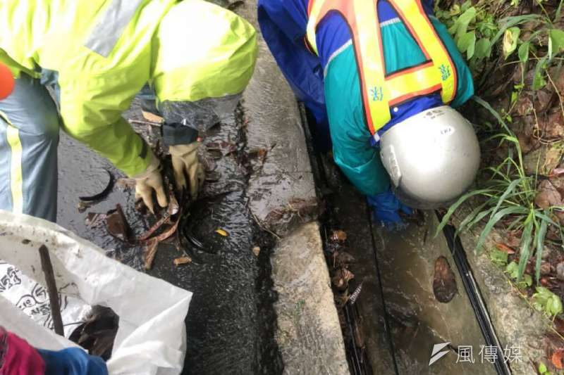 清潔隊員巡檢各轄區易積水地區與側溝洩水孔及排水口,如有樹葉垃圾堵塞情況,立即排除以維持排水暢通。(圖/徐炳文攝)