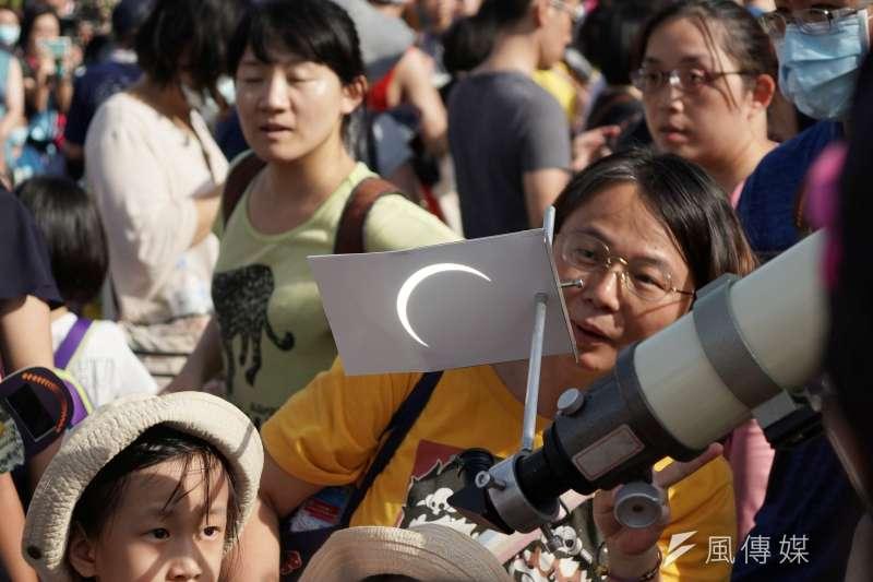 天文奇景日偏食21日登場,民眾聚集於台北市天文館外透過望遠鏡反射觀看日蝕狀況。(盧逸峰攝)