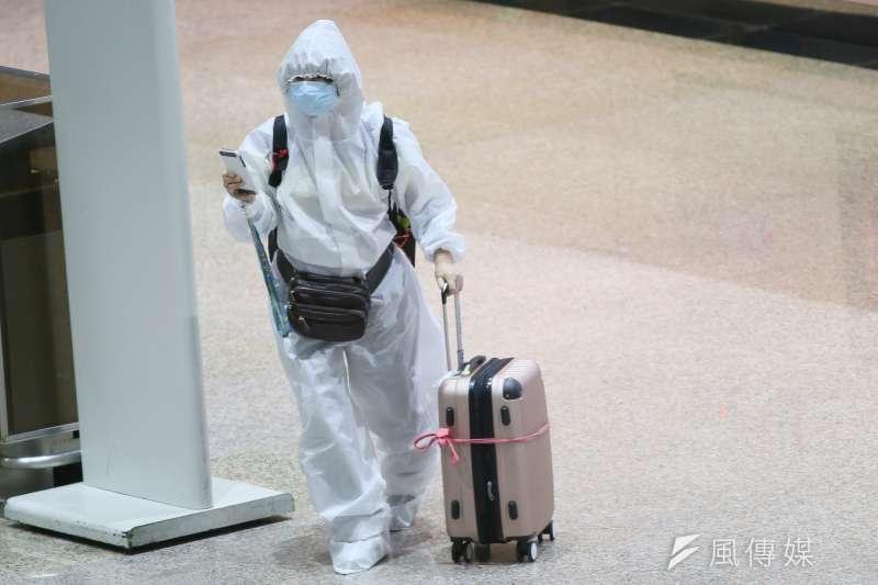 因應疫情壓力,搭機往往得要穿防護衣、戴口罩全副裝備。(柯承惠攝)