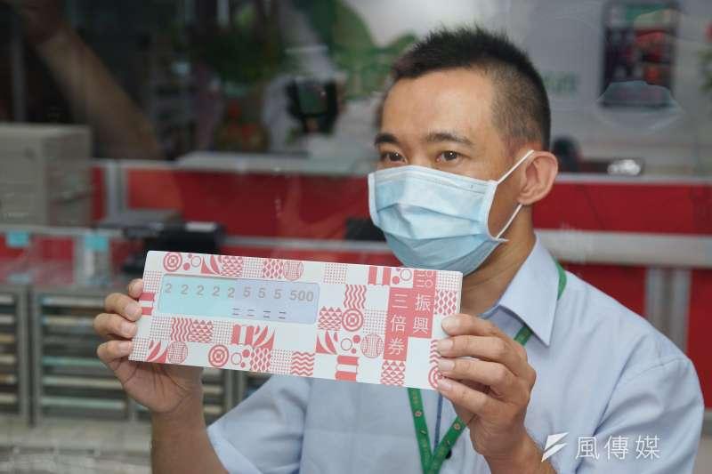 三倍券引發部分民眾抱怨領用複雜、錢太少,民進黨桃園市議員王浩宇認為,將台灣與疫情嚴重的國家比較振興政策是不合理的。圖為郵局員工展示三倍券樣張。(資料照,盧逸峰攝)