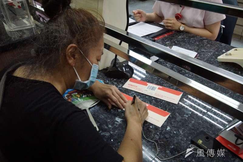 20200715-全台郵局15日起開放購領振興三倍券,民眾辦理領取手續。(盧逸峰攝)