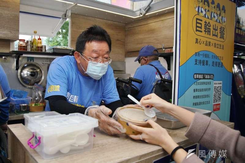 20201214-新巨輪服務協會推出無礙餐車,讓協會成員能生活自立,圖為協會理事長陳安宗現做餐點遞給顧客。(盧逸峰攝)