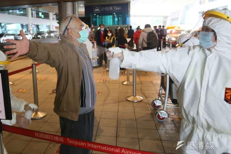 20210126-桃園機場入境旅客接受清潔消毒。(柯承惠攝)