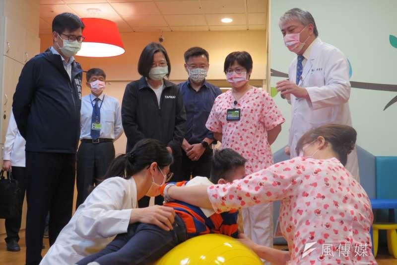 總統蔡英文訪視飛象家園,由市長陳其邁陪同,了解與孩童互動的過程,復健師讓孩童趴臥在瑜珈球上練習肢體伸展。(圖/徐炳文)