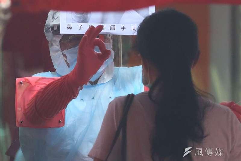 新北市政府在中和區積穗活動中心成立快篩站,一位執勤的醫護人員為民眾完成採檢後,做出OK的手勢。(柯承惠攝)