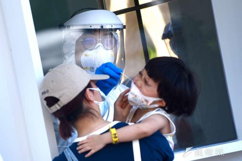 本土新冠肺炎日前曾一度趨緩,但近日又呈現升溫趨勢,圖為家長帶小孩接受快篩檢測。(顏麟宇攝)