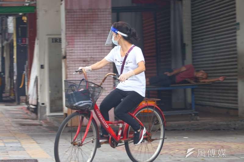 20210605-疫情下的萬華,民眾騎車外出配戴口罩面罩,但遠方仍有街友未戴口罩。(顏麟宇攝)