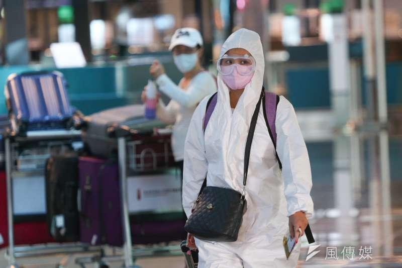 五月疫情爆發,赴美打疫苗時有所聞。圖為旅客著防護衣配戴口罩及眼罩辦理出境手續。(顏麟宇攝)