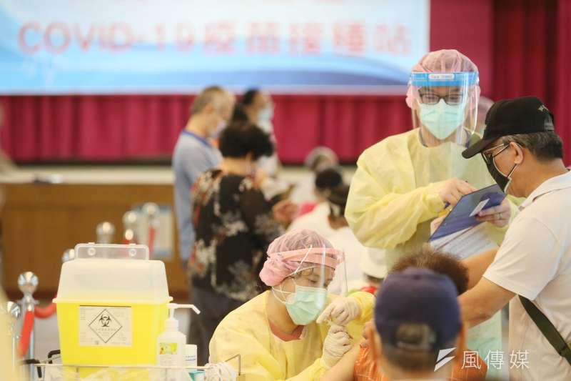 台灣開始為高齡老人打疫苗,但疫苗分配一度成為政治鬥爭焦點。圖為新北市三重區小巨蛋體育館接種站醫護人員為長者施打疫苗情形。(柯承惠攝)