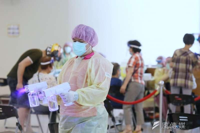 20210615-台灣新冠肺炎疫情三級警戒,各地疫苗接種站16日為民眾施打新冠肺炎疫苗,圖為新北市三重區小巨蛋體育館接種站為長者施打疫苗,醫護人員在旁消毒。(柯承惠攝)