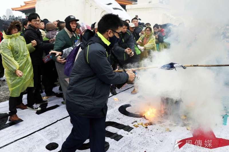 20170228-獨派團體下午在自由臺灣黨主席蔡丁貴的帶領下,前往中正紀念堂,想要前進到蔣中正銅像大廳表達訴求,過程遭警方攔阻,隨後退回自由廣場牌樓下,並焚燒中華民國國旗表達訴求。圖為焚燒國旗時,一旁警員衝出撲滅。(蘇仲泓攝)