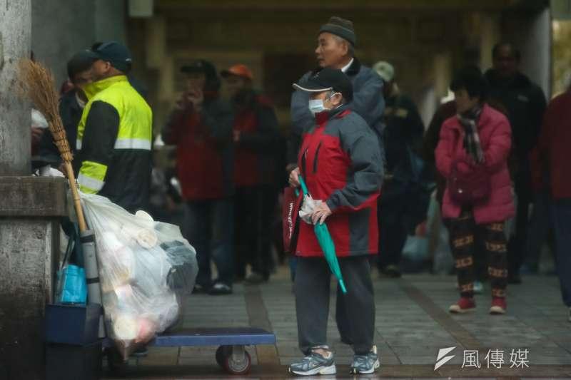 最強寒流23日來襲,萬華地區街友也穿上圓夢關懷協會提供的外套禦寒。(顏麟宇攝)