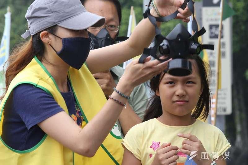 606反空污大遊行中,小朋友戴上防毒面具,象徵連呼吸一口新鮮空氣都困難。(林韶安攝)