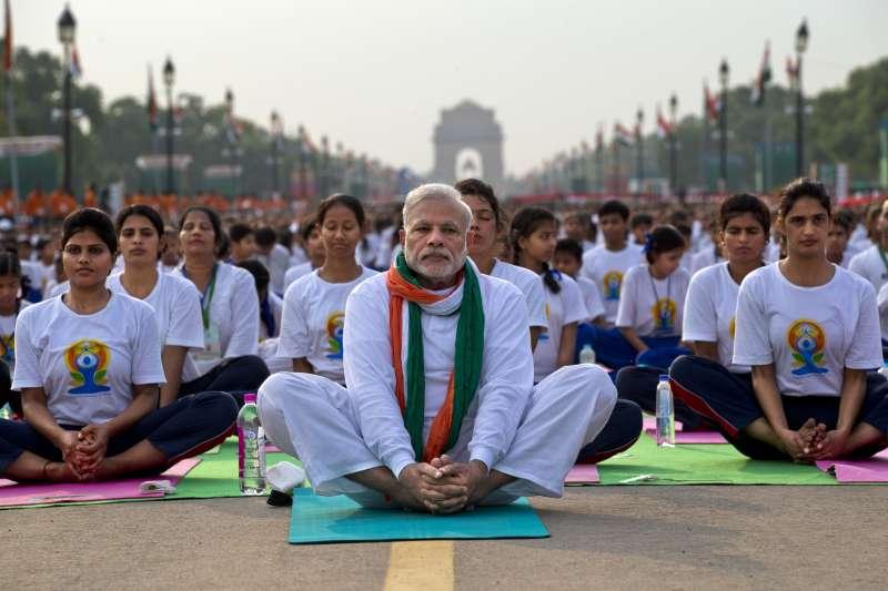 民主國家治理問題的核心,在於「盲目民粹」的盛行。一位美籍印度裔經濟學家普拉納布.巴丹,在其所著《覺醒的泥足巨人》中,指出了印度民主制度的12個盲點。圖為印度總理莫迪(前排中)帶領群眾齊做瑜珈。(資料照,美聯社)
