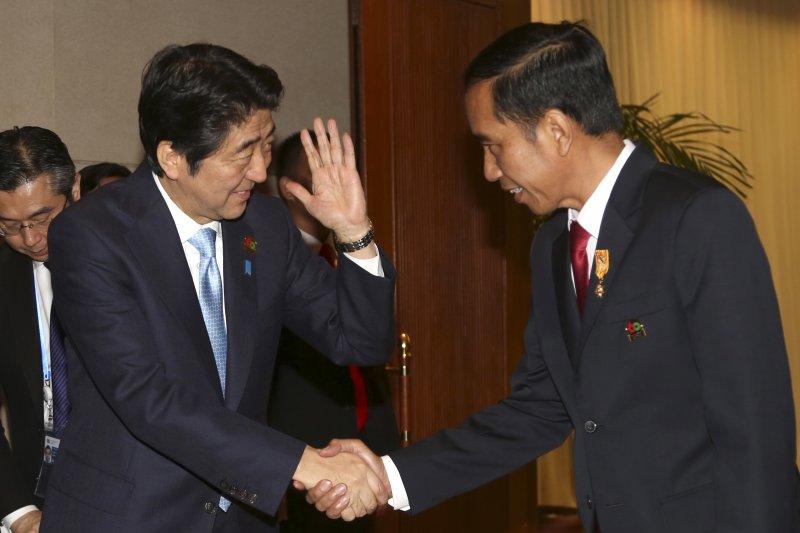 東道主印尼總統佐科威(右)與日相安倍晉三。(美聯社)