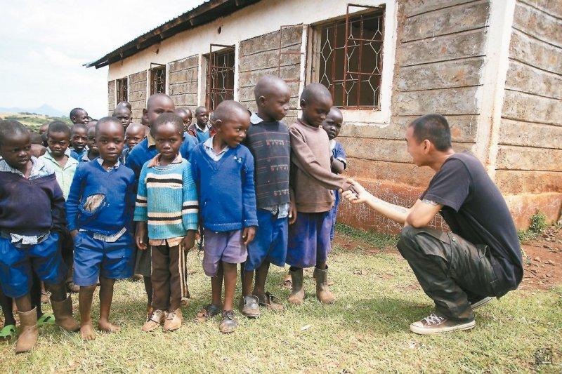 「舊鞋‧救命」活動發起人楊右任與肯亞兒童。(取自宏觀僑務新聞網)