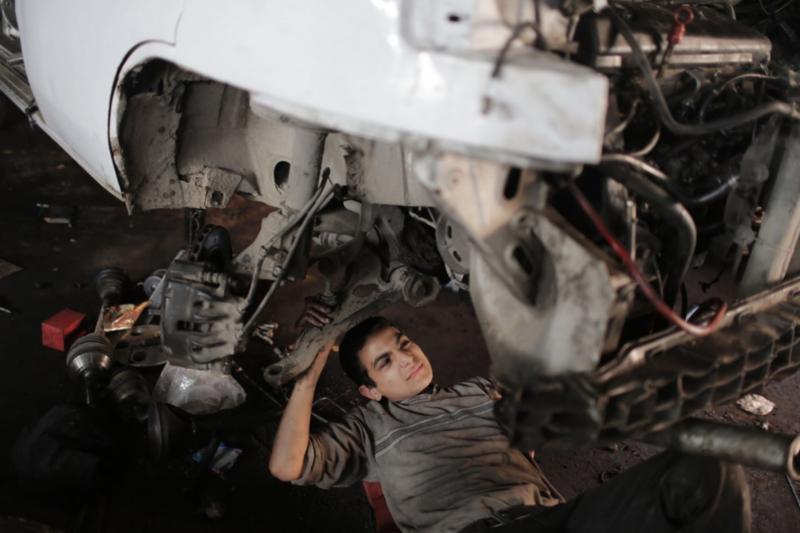 12歲的馬哈茂德·沙班在加薩走廊的一家汽車修理店工作。(新華社)