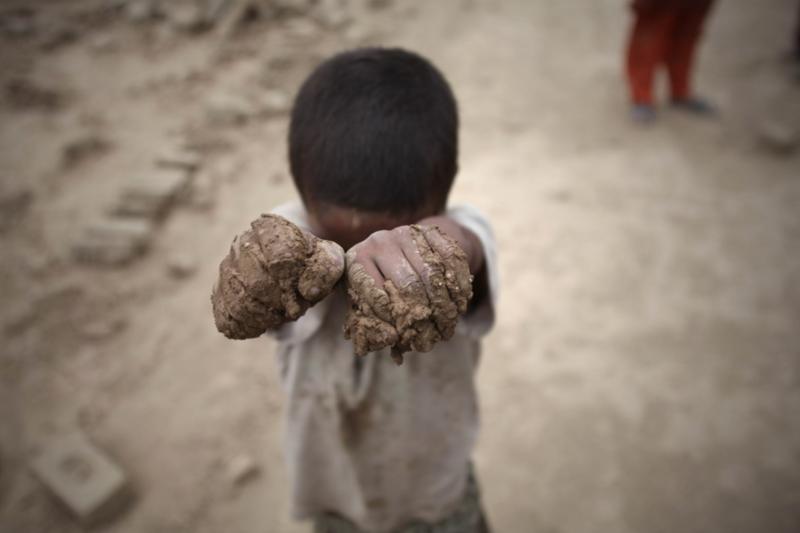 在阿富汗首都喀布爾的一個磚廠,一名小男孩展示自己沾滿泥土的雙手。(新華社)