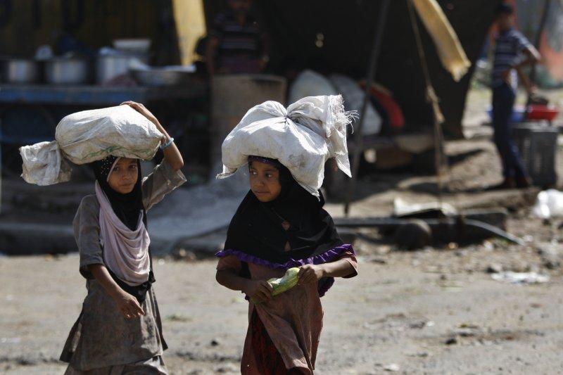 兩位印度小朋友在反童工日當天,各頂著一袋撿拾來的菜葉要去賣。(美聯社)