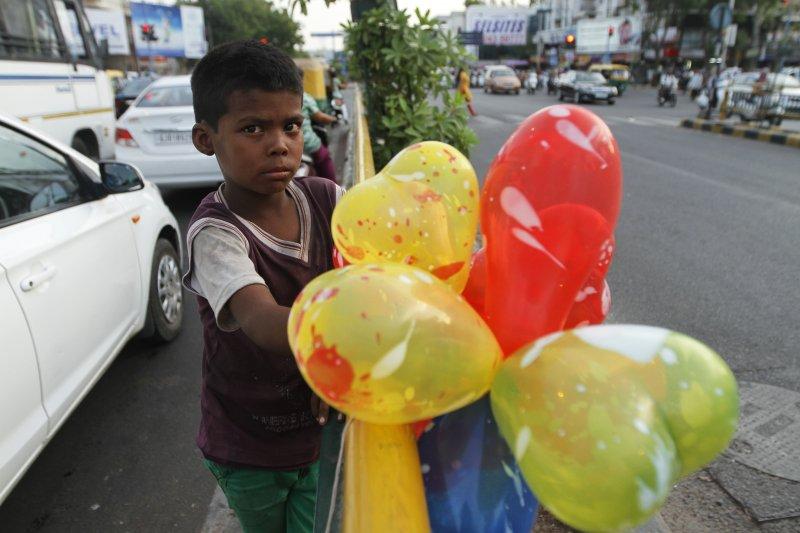 一名印度學童在亞美達巴德街頭兜售氣球。(美聯社)