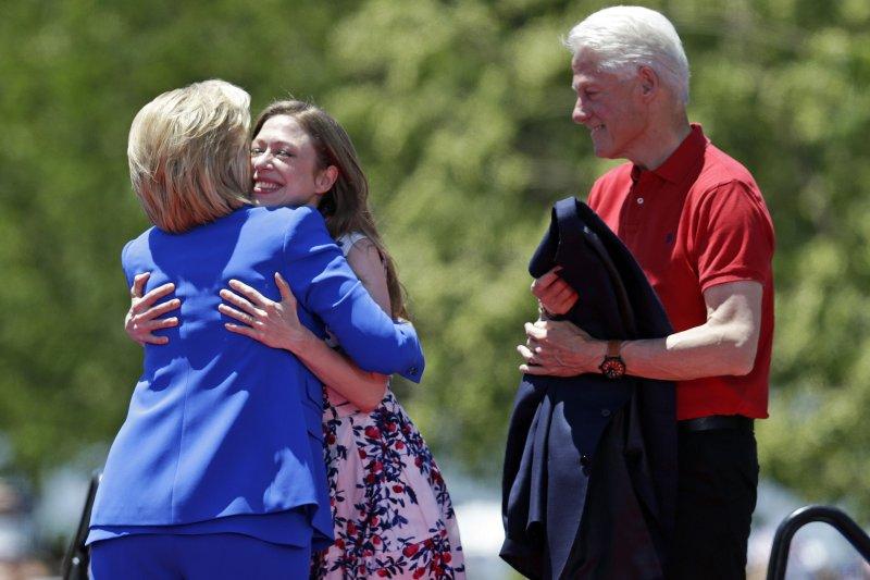 希拉蕊13日與女兒雀兒喜(中)擁抱,夫婿柯林頓(右)也到場。(美聯社)