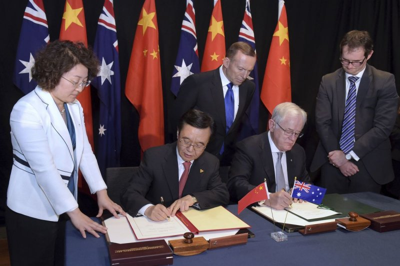 中國商務部部長高虎城(左二)與澳洲貿易與投資部部長羅布(右二)17日在坎培拉簽署《中澳自由貿易協定》,澳洲總理亞伯特(中)也出席簽字儀式。