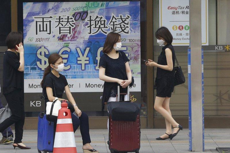 首爾街頭戴著口罩的年輕女性。(美聯社)