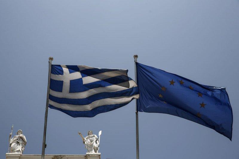 希臘國旗(左)與歐盟旗幟還能一起飄揚多久?22日的會議將是關鍵。(資料照,美聯社)