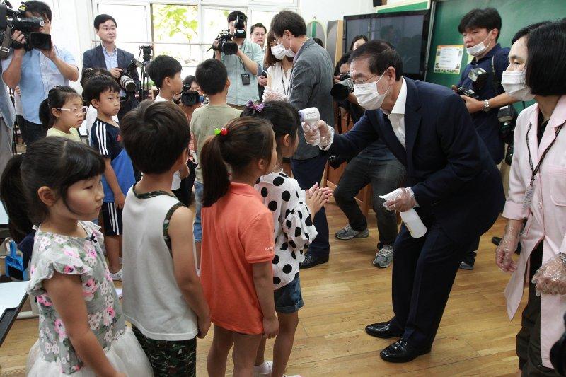 首爾市長朴元淳幫小朋友量體溫。(美聯社)